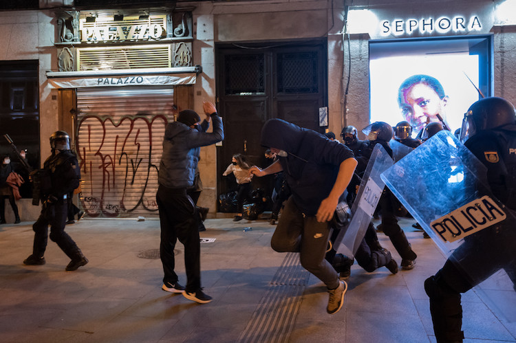Riot police beating protesters during clashes in a